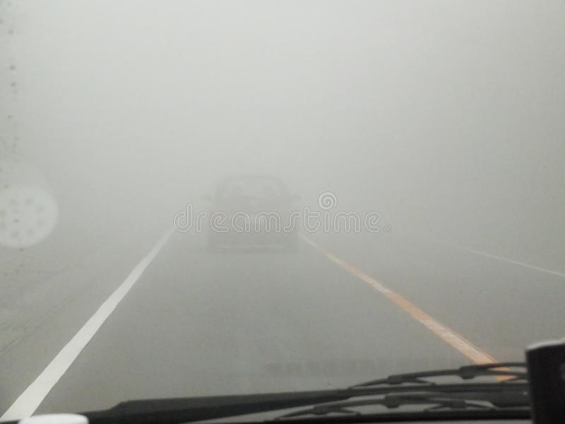 Foggy road. Driving on a foggy road with almost zero visibility stock images