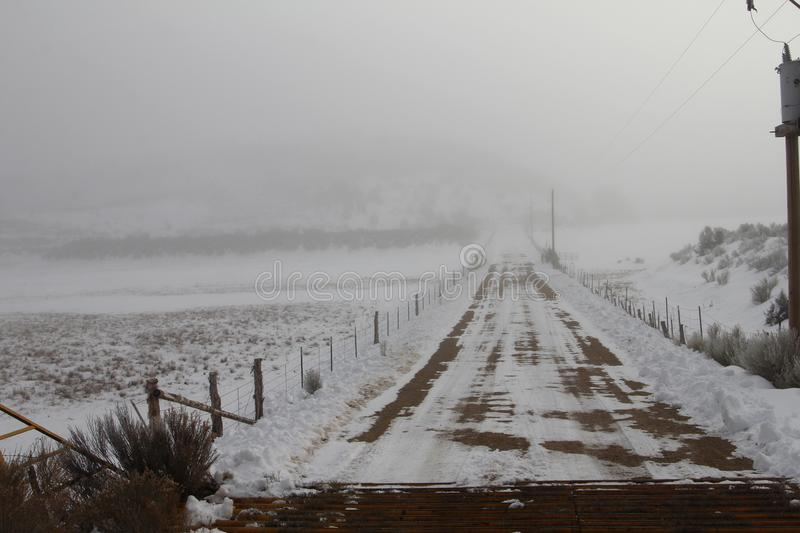 Foggy Road to nowhere, snow covered tracks royalty free stock photography