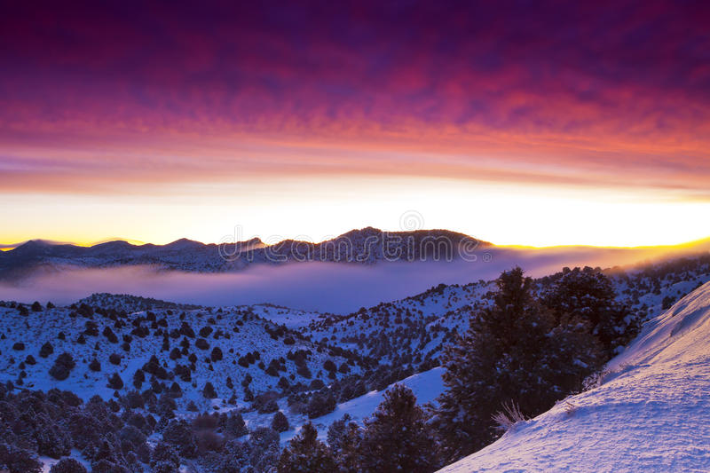Foggy Sunrise. Sunrise near Virginia City, Nevada. Mountain ranges with rocks and pine trees covered in snow with vivid colored skies stock image