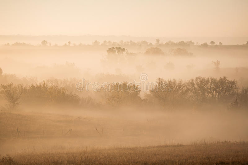 Foggy sunrise. Horizontal image of the sun rising on a foggy Autumn morning in the Flint Hills of Kansas royalty free stock image