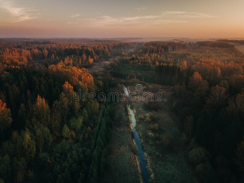 Foggy sunrise over river surrounded by agriculture fields and woods. Early autumn. stock image