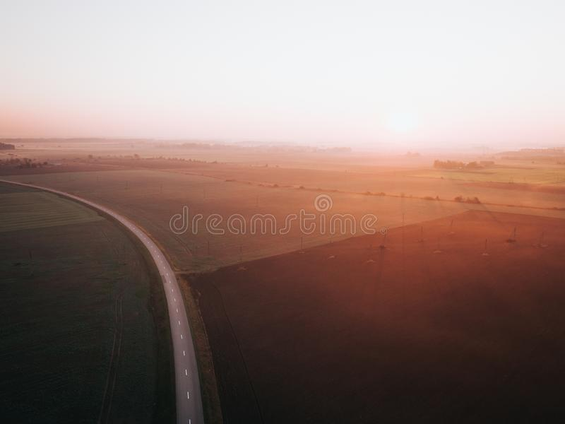Foggy sunrise over road surrounded by agriculture fields. Early autumn. stock photography