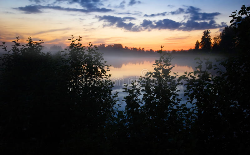 Foggy sunset. Near the lake. Summer stock photos