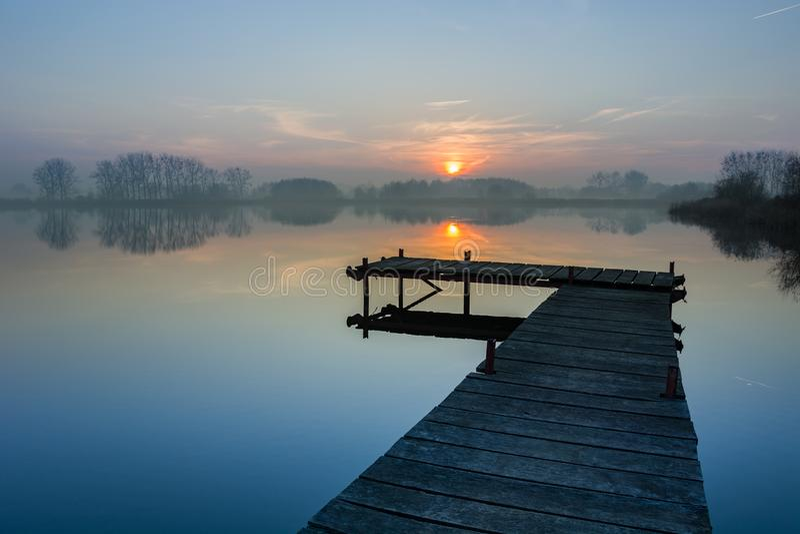 Foggy sunset at the lake stock photos