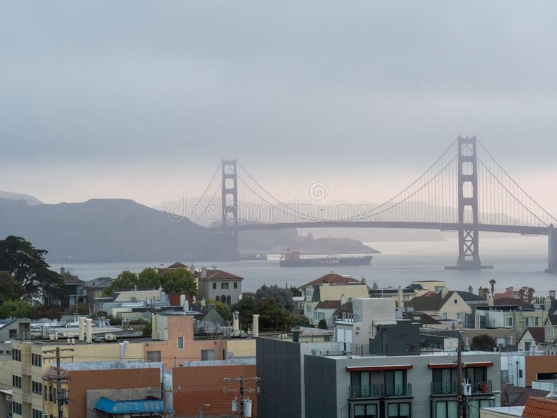 Foggy view of Golden Gate Bridge and Marin Headlands with cargo ship passing royalty free stock photography