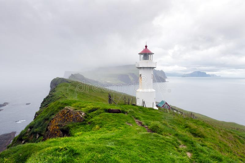 Foggy view of old lighthouse on the Mykines Island obrazy royalty free