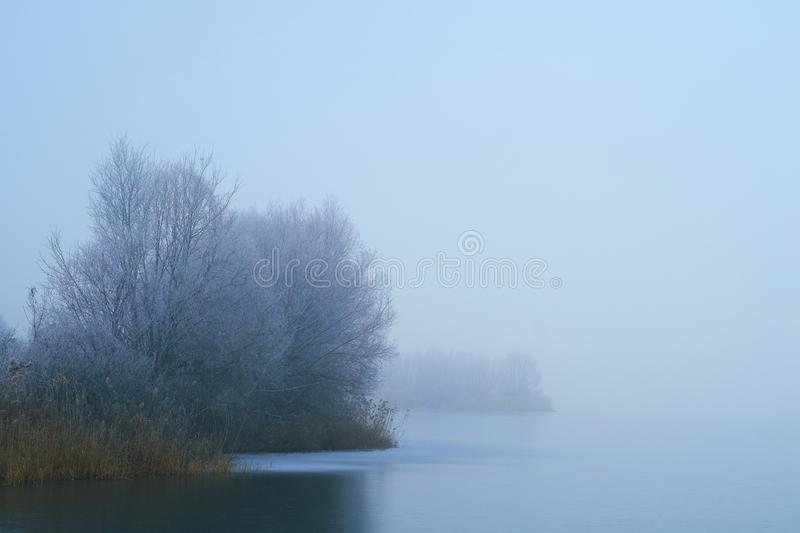 Foggy winter frozen lake royalty free stock images