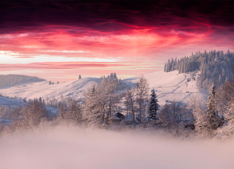 Foggy winter landscape in mountain village. Under the dark red sky royalty free stock photos