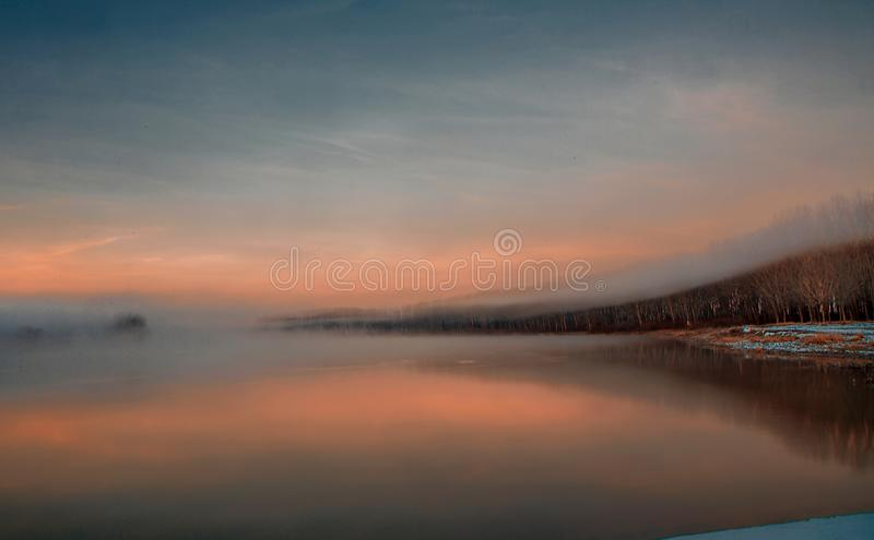 Foggy Winter Morning. A foggy winter morning at the Danube River in Romania. The thin fog rose just above the tree tops, offering us a wonderful landscape stock photography
