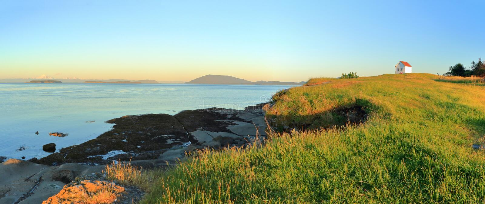 Foghorn Station and Rosario Strait in Evening Light at East Point on Saturna Island, Gulf Islands National Park, British Columbia. Panorama of coastal landscape royalty free stock image