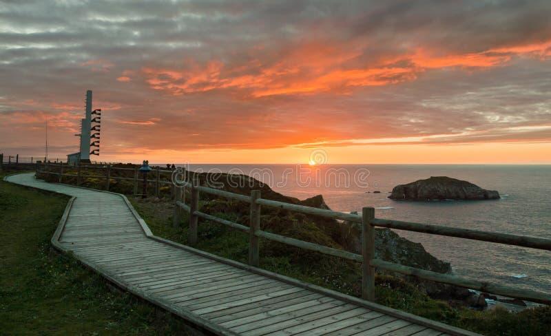 Foghorn and wooden walkway near lighthouse Peñas Cape on a beautiful sunset Coast of Asturias, Spain royalty free stock photos