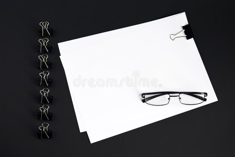 Fogli bianchi, bicchieri e dispositivo di aggancio per legatura di fogli di carta sullo sfondo nero, vista superiore, presa in gi fotografia stock libera da diritti