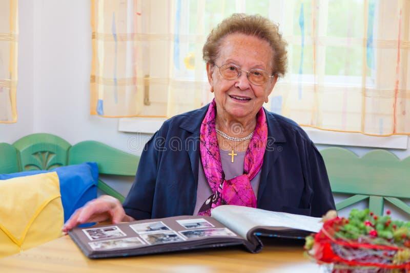 Fogli degli anziani attraverso un album di foto immagini stock