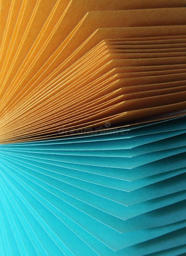 Fogli di carta multicolori per le note di registrazione su un turchese e su un giallo della superficie piana fotografie stock libere da diritti