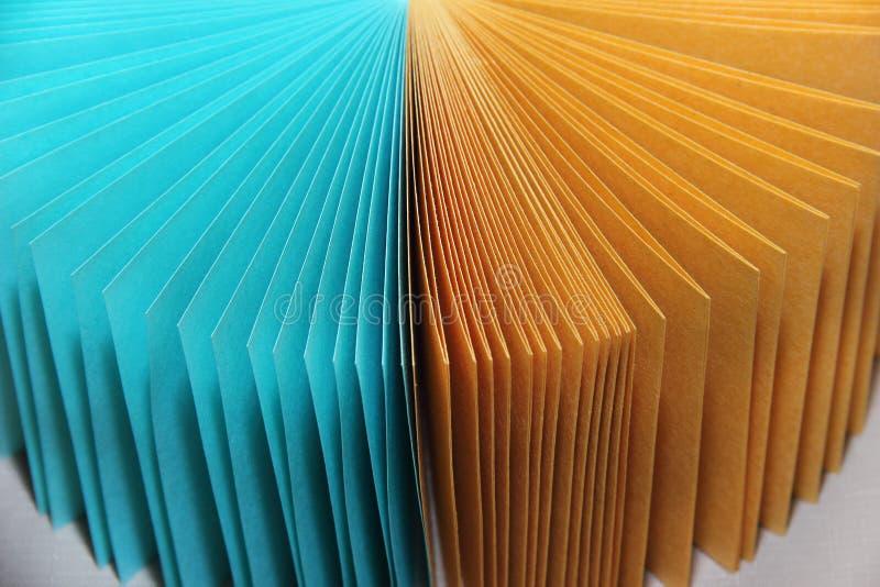 Fogli di carta multicolori per le note di registrazione su un turchese e su un giallo della superficie piana fotografia stock