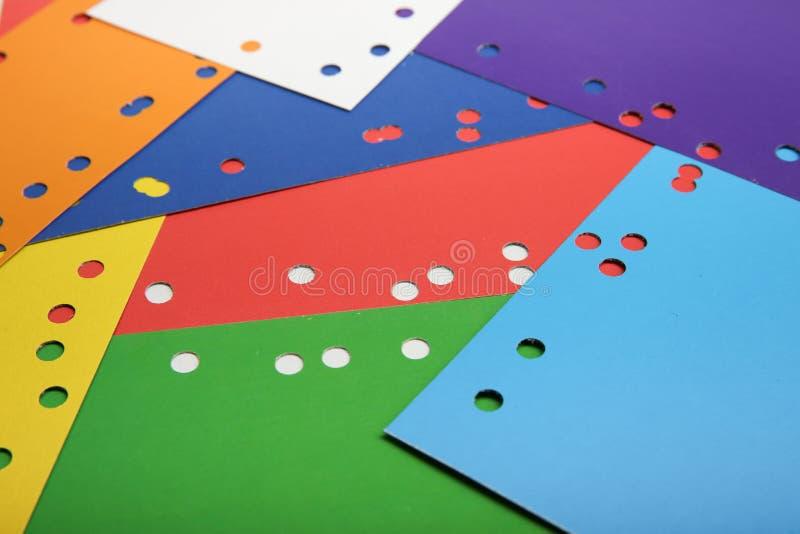 Fogli di carta variopinti con i fori fatti dal puncer immagine stock