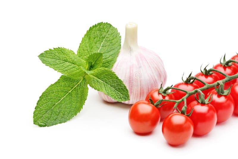 Fogli di menta, aglio e pomodori di ciliegia immagine stock libera da diritti