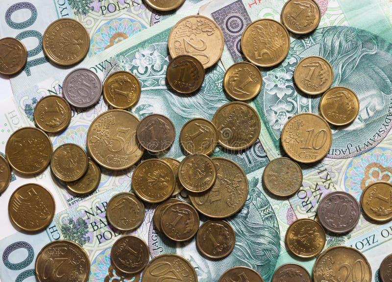 Fogli piatti di monete miste isolate su fondo bianco Miscela di centesimi di euro e di grosz di monete polacche sulle banconote d fotografie stock libere da diritti