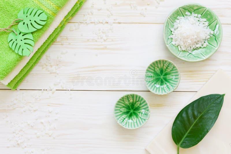 Foglia della pianta verde, sale marino aromatico ed asciugamani o Foto alta vicina su di legno bianco fotografia stock libera da diritti