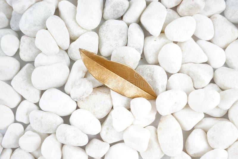 Foglia dorata isolata sulla pietra bianca cobblestone Foglia di oro Struttura della priorità bassa immagine stock libera da diritti