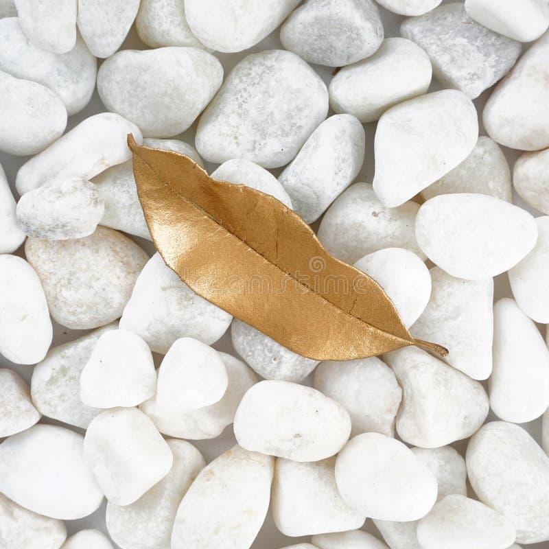 Foglia dorata isolata sulla pietra bianca cobblestone Foglia di oro Struttura della priorità bassa fotografie stock