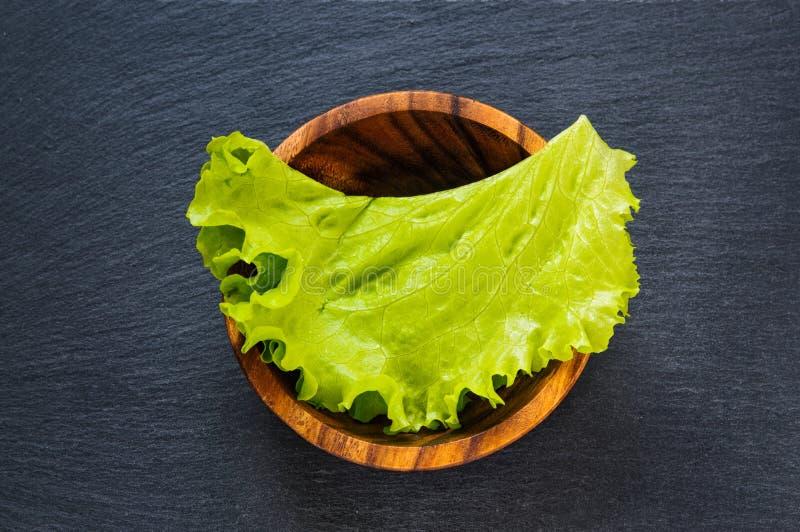 Foglia verde fresca della lattuga in ciotola di legno sulla pietra nera dell'ardesia come fondo dell'alimento del modello Vista p fotografia stock libera da diritti