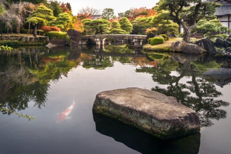 Fogliame spettacolare di autunno e un ponte sopra lo stagno ai giardini Koko-en a Himeji, Giappone fotografia stock libera da diritti