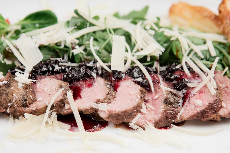 Foglie arrostite della carne e degli spinaci dell'anatra in piatto bianco su fondo di legno nero immagine stock