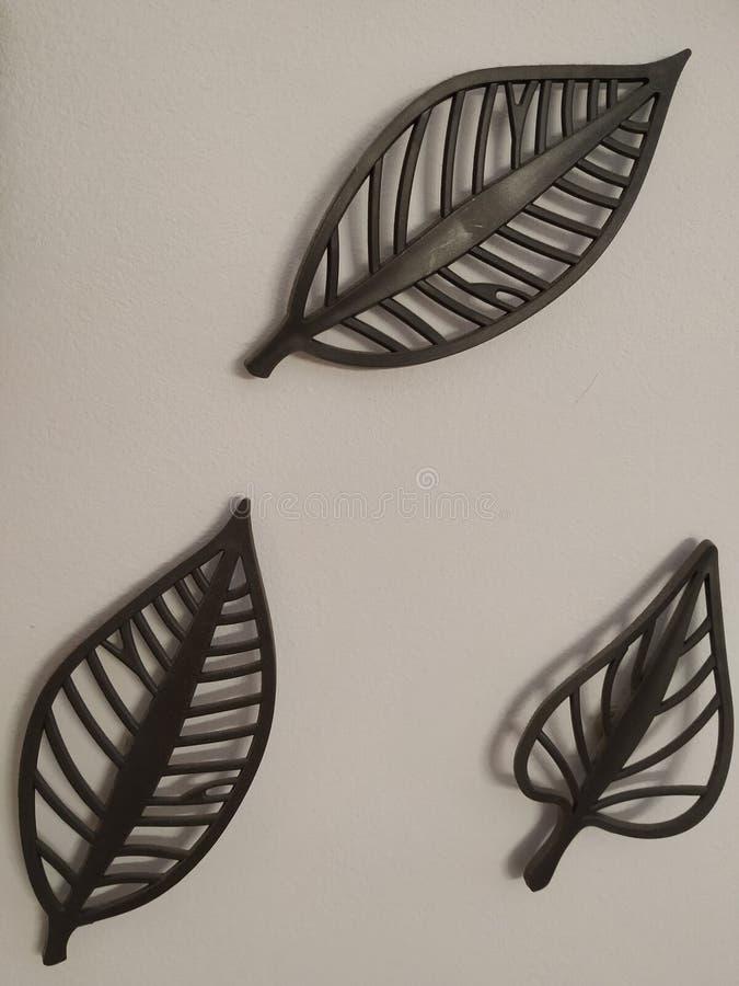 Foglie decorative del metallo tre sulla parete bianca fotografia stock libera da diritti