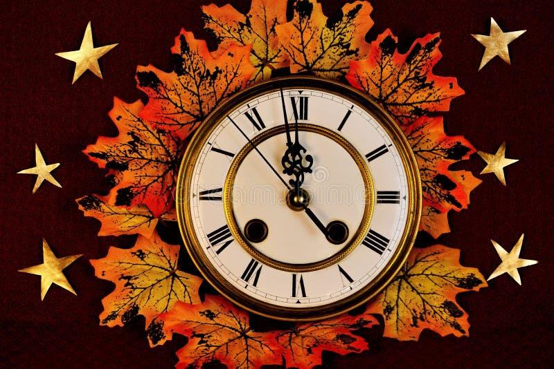 Foglie di acero di autunno, colori differenti di giallo, oro e rosso sui precedenti degli orologi d'annata, immagine stock