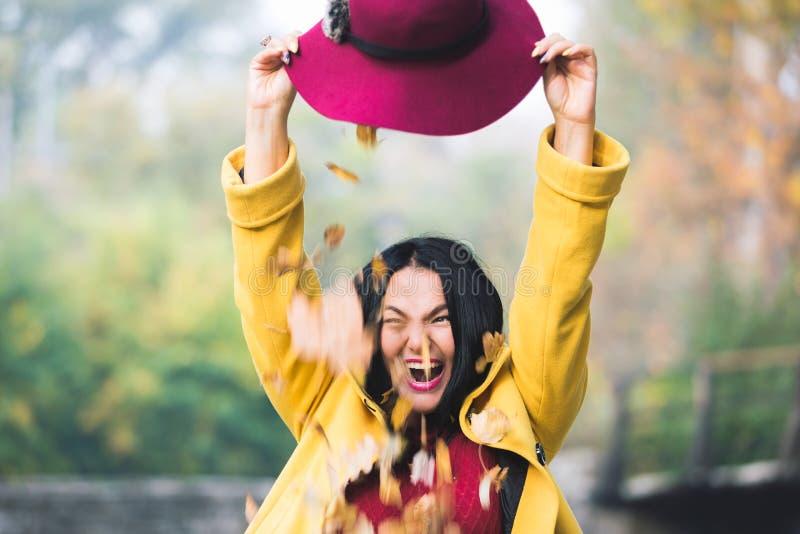 Foglie di autunno che cadono da un cappello sulla donna felice fotografie stock