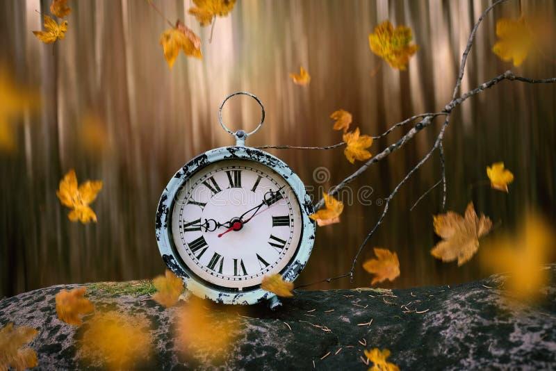 Foglie di autunno che soffiano attraverso una sveglia antica immagini stock