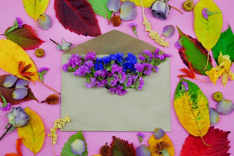 foglie di autunno variopinte con la busta e fiori su fondo porpora fotografia stock libera da diritti