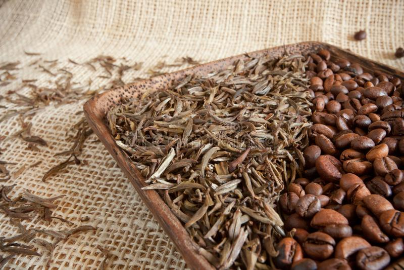Foglie di tè secche e chicchi di caffè arrostiti: theine contro caffeina fotografie stock libere da diritti