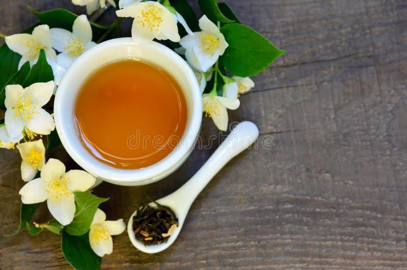 Foglie di tè verdi asciutte del gelsomino in un cucchiaio con i fiori del gelsomino e la tazza di tè su vecchio fondo di legno Be immagini stock libere da diritti