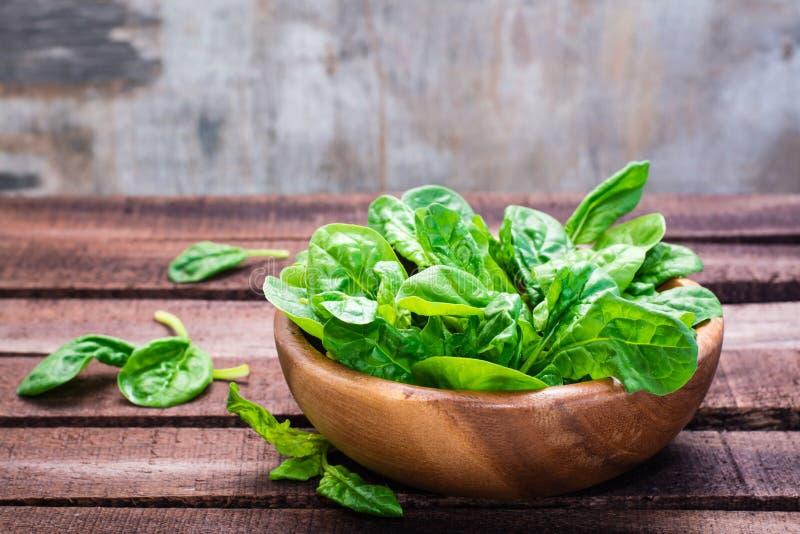 Foglie fresche degli spinaci del bambino in una ciotola fotografie stock