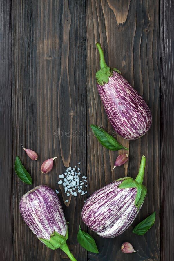 Foglie porpora della melanzana, dell'aglio e del basilico da sopra sul bordo di legno anziano con lo spazio del testo Raccolto fr fotografie stock