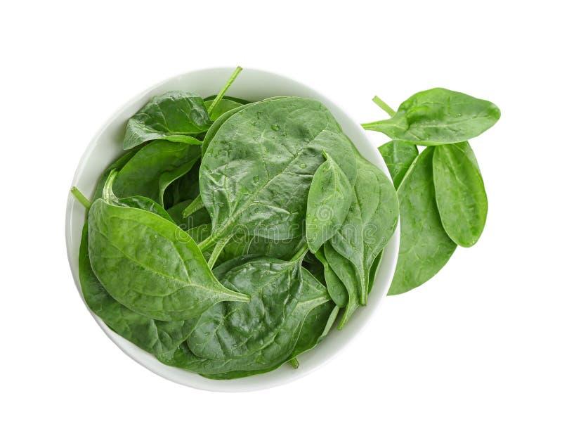 Foglie sane verdi fresche degli spinaci del bambino in ciotola ceramica sulla vista bianca e superiore fotografia stock libera da diritti
