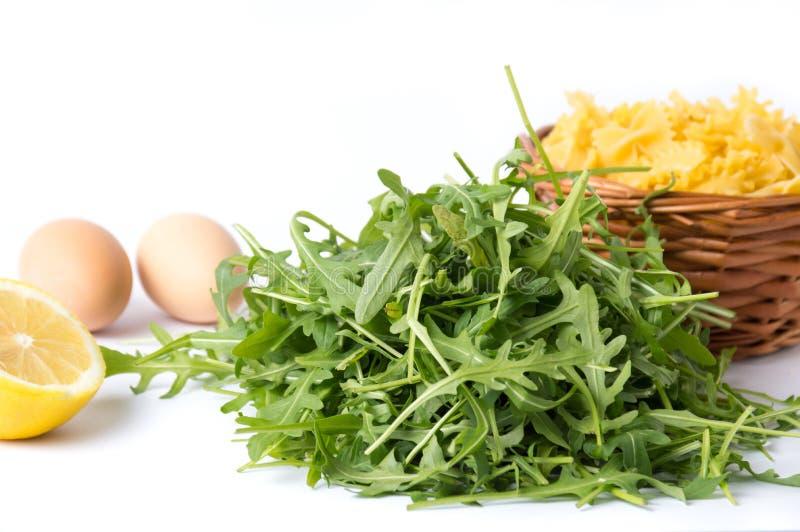 Foglie verdi della pianta di Rucola ed ingredienti della pasta immagini stock