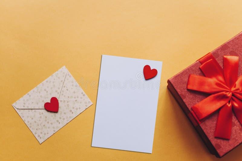 Foglio bianco con cuore rosso per testo o scrivere Vicino ad una busta con un cuore da inviare e ad una scatola con un regalo fotografia stock