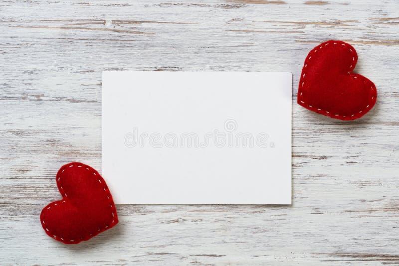 Foglio bianco di carta e dei cuori rossi di amore fotografie stock libere da diritti