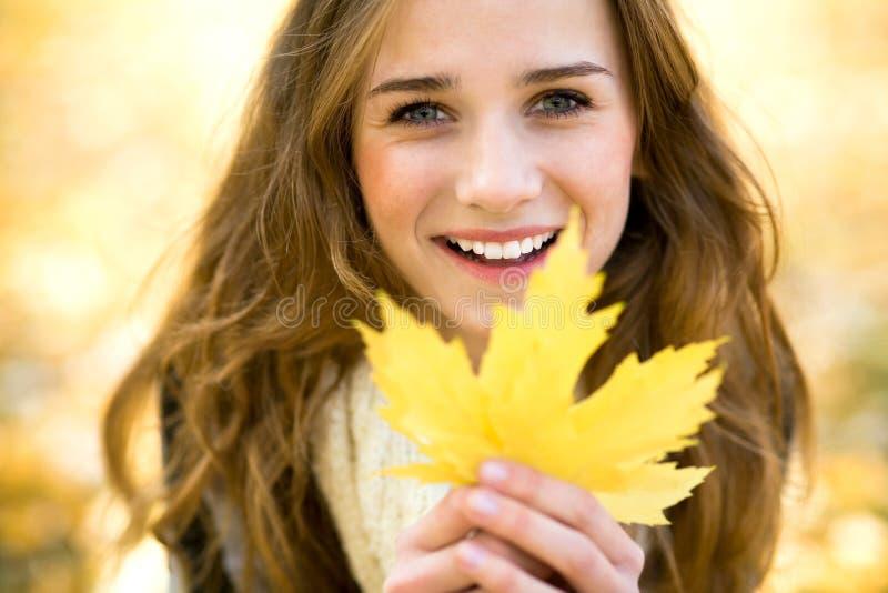 Foglio di autunno della holding della donna fotografia stock