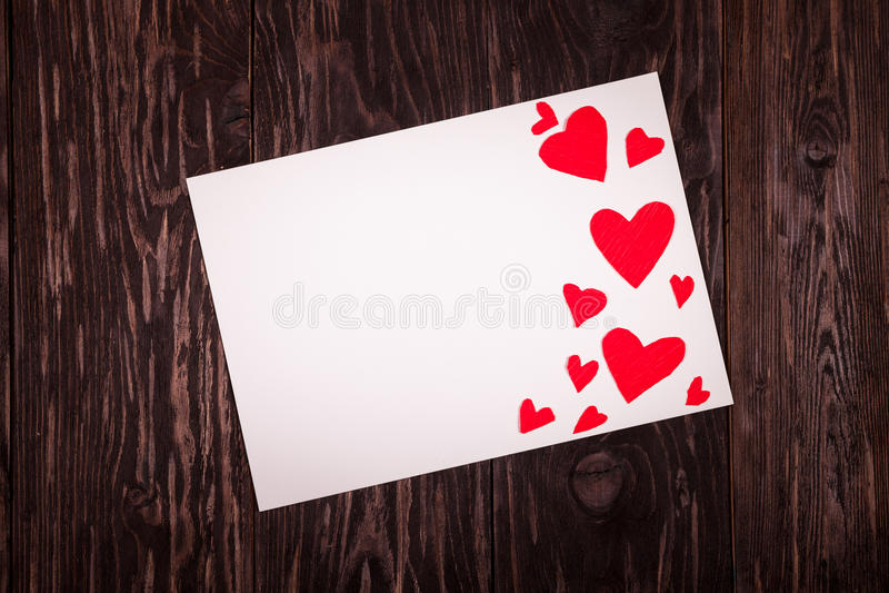 Foglio di carta bianco il fondo di legno dei piccoli cuori rossi immagini stock