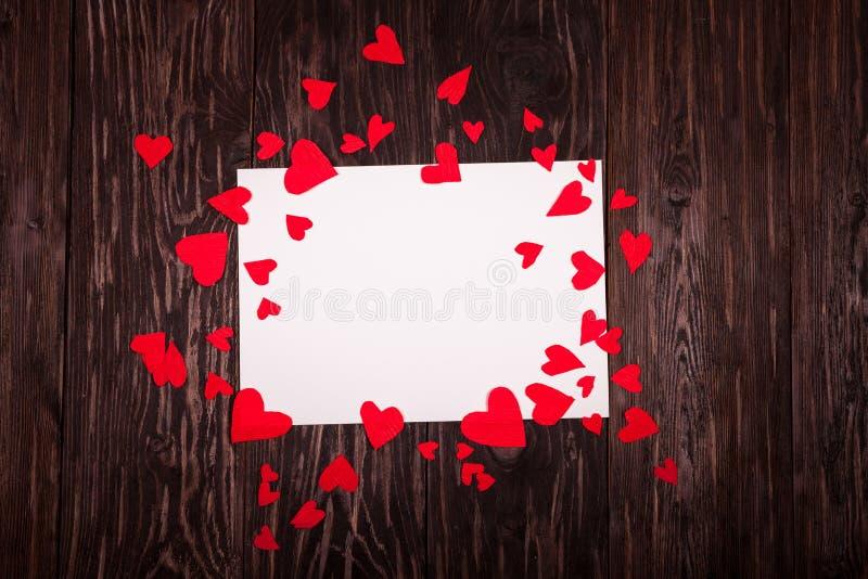 Foglio di carta bianco il fondo di legno dei piccoli cuori rossi fotografia stock