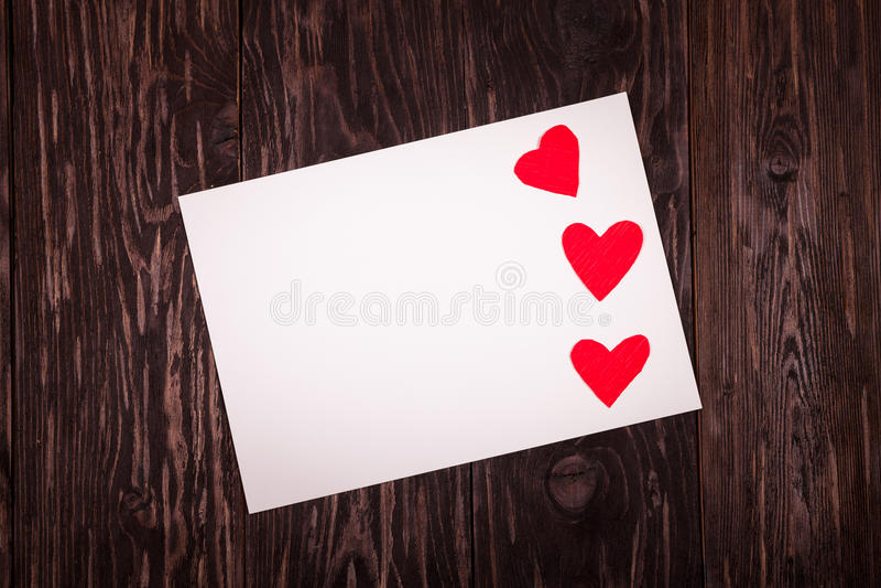 Foglio di carta bianco il fondo di legno dei piccoli cuori rossi fotografie stock