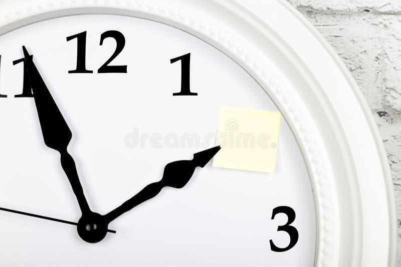 Foglio di carta vuoto come ricordo sull'orologio Vista del primo piano immagine stock