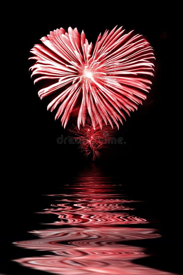 Fogo de artifício vermelho na forma de um coração, água foto de stock