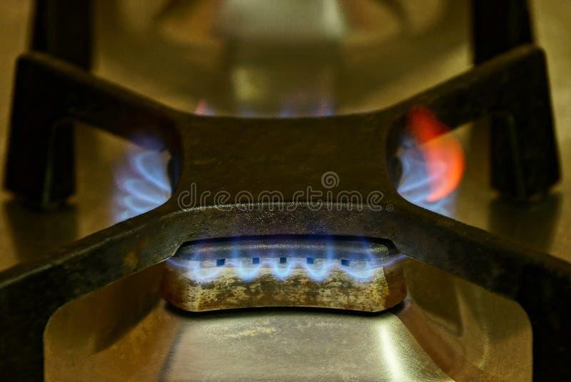Fogo de um queimador de gás preto em uma placa do ferro fotografia de stock