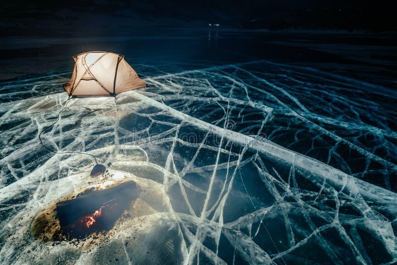 Fogo no gelo na noite Acampamento no gelo A barraca está ao lado da fogueira Lago Baikal Próximo há carro Barraca de abrigo e fotos de stock royalty free