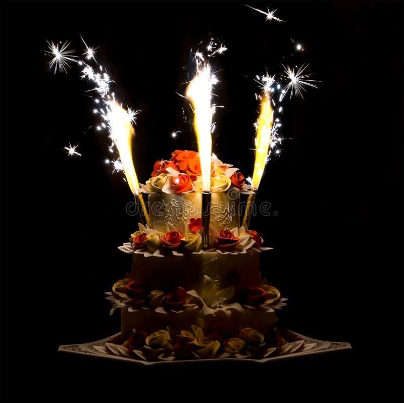 Fogos de artifício coloridos do bolo brilhante festivo em um fundo escuro que contrasta o fundo colorido do casamento que comemor fotos de stock royalty free